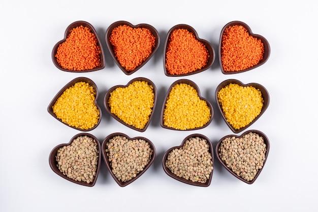 Algumas lentilhas amarelas, verdes e vermelhas em tigelas em forma de coração