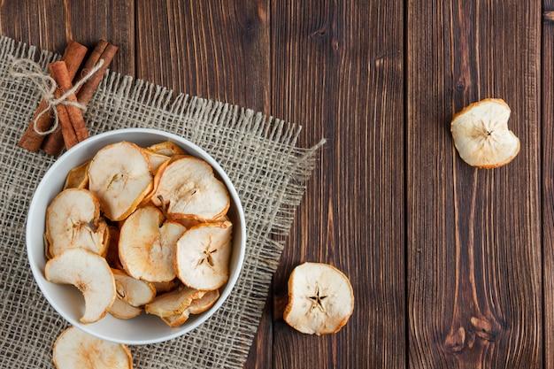 Algumas maçãs secas com canela seca em uma tigela no pano e fundo de madeira, vista superior.