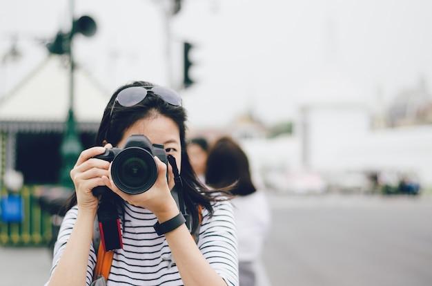 Algumas mulheres seguram a câmera dslr na mão e tiram uma foto na cidade