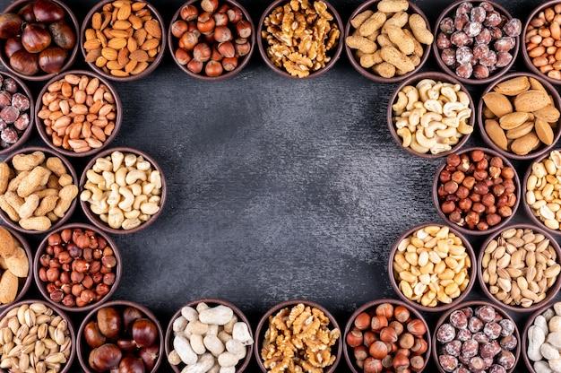 Algumas nozes sortidas e frutas secas com nozes, pistache, amêndoa, amendoim, em uma mini tigelas diferentes