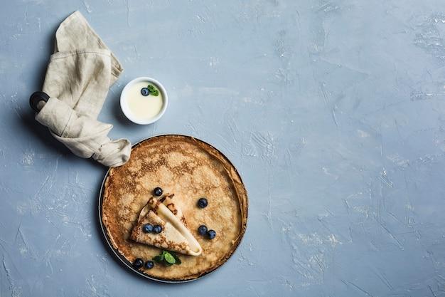 Algumas panquecas em uma panela com mirtilos e hortelã, com leite condensado em uma molheira sobre um fundo azul claro.
