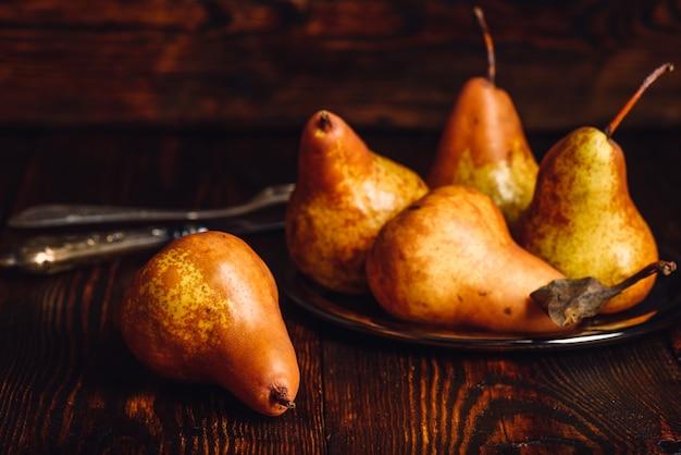 Algumas peras douradas com garfo e faca na mesa de madeira.