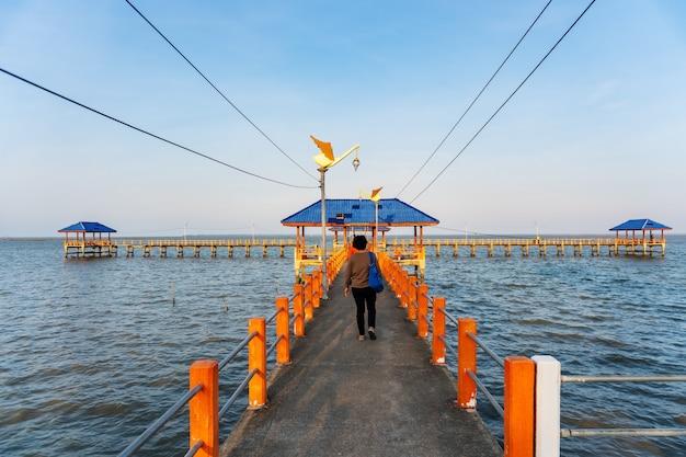 Algumas pessoas andando na ponte no mar azul