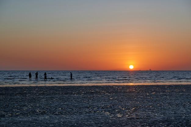 Algumas pessoas estão na praia durante o pôr do sol