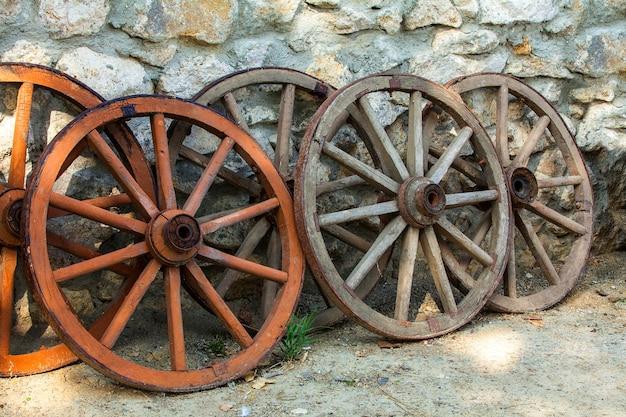 Algumas rodas históricas de carrinho de madeira desbotada e abandonadas juntas