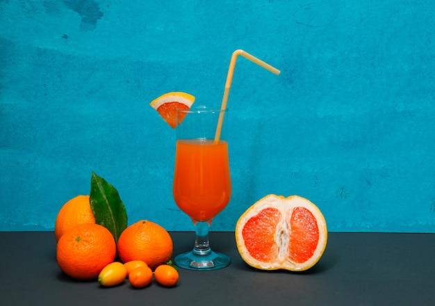 Algumas tanjerinas com laranja e suco na superfície textured azul, vista lateral.