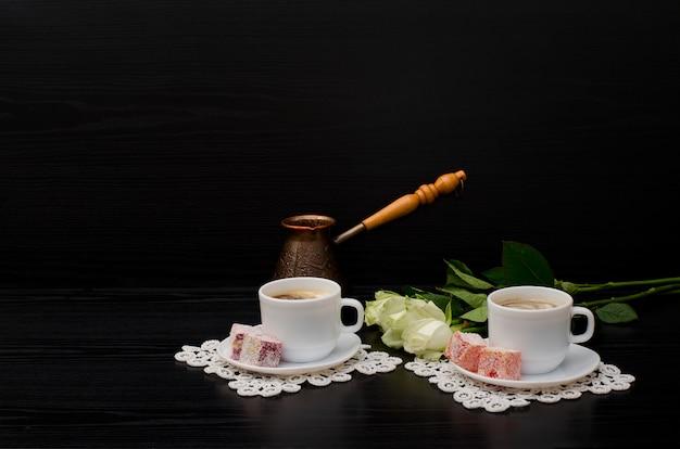 Algumas xícaras de café com leite, cezve, turkish delight, um buquê de rosas brancas. espaço para texto