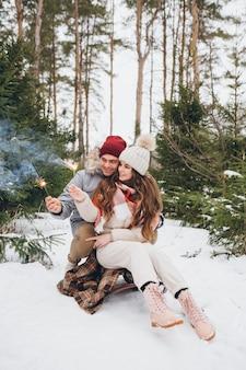 Alguns abraços e queimam fogos de artifício em uma floresta de coníferas de inverno enquanto estão sentados em um trenó