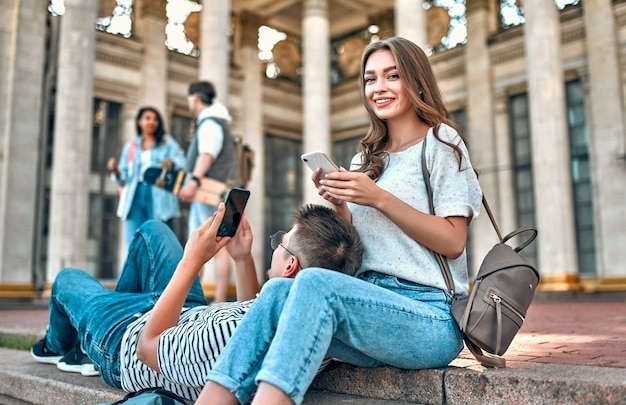 Alguns alunos com mochilas e um laptop sentam-se nos degraus fora do campus e usam seus smartphones.