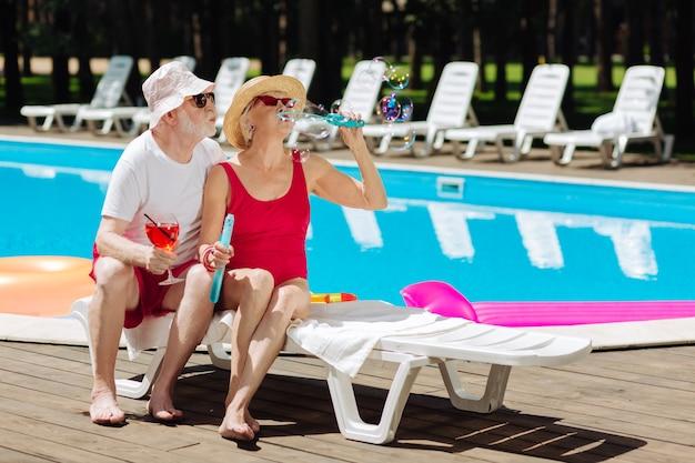 Alguns aposentados bonitos e elegantes soprando bolhas de sabão enquanto estão sentados perto da piscina