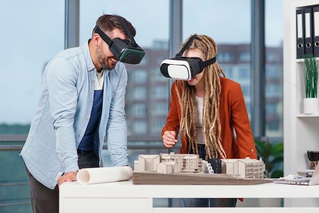 Alguns arquitetos ou engenheiros em óculos de realidade virtual trabalhando com a maquete da futura área residencial em um escritório moderno