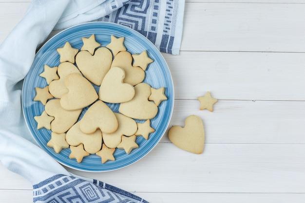 Alguns biscoitos em um prato no fundo de madeira e toalha de cozinha, vista superior.