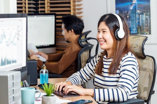 Alguns colegas asiáticos sorrindo e trabalhando com o computador no escritório doméstico quando covid19
