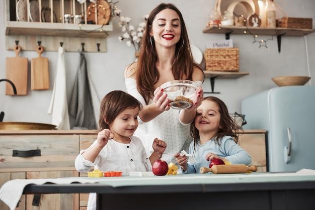 Alguns doces não interferem. jovem mulher bonita dar os biscoitos enquanto eles sentados perto da mesa com brinquedos