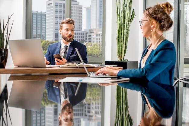 Alguns gerentes de alto escalão trabalhando com laptops e documentos sentados no interior do escritório de luxo com uma bela vista dos arranha-céus