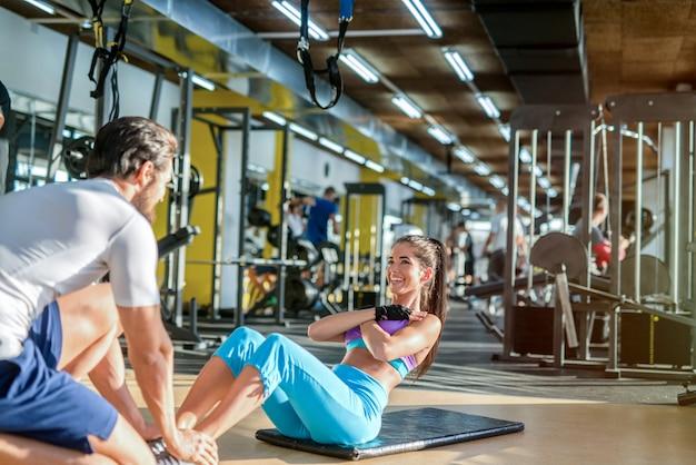 Alguns gols. é um casal forte malhando em uma academia. homem ajudando a garota com abdominais.
