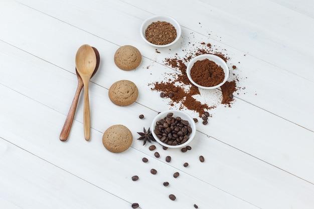 Alguns grãos de café com biscoitos, colheres de madeira, café moído em uma tigela sobre fundo de madeira, vista de alto ângulo.
