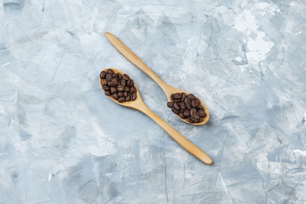 Alguns grãos de café em colheres de madeira em fundo de gesso cinza, plana leigos.