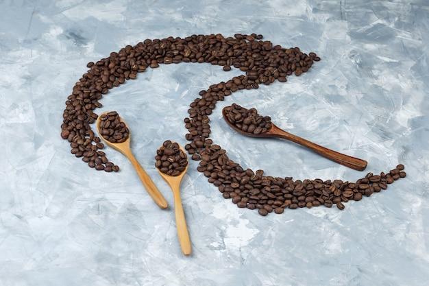 Alguns grãos de café em colheres de madeira em fundo de gesso cinza, vista de alto ângulo.