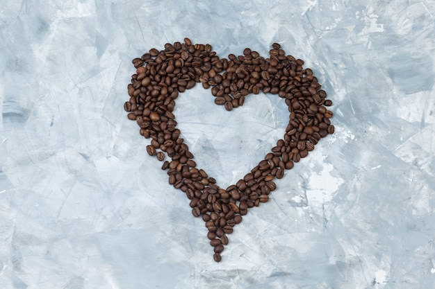Alguns grãos de café em fundo de gesso cinza, plana leigos.