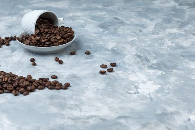 Alguns grãos de café na xícara e prato em fundo de gesso cinza, vista de alto ângulo.