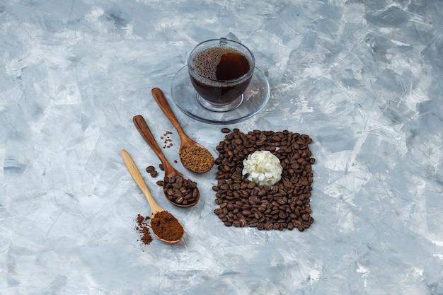 Alguns grãos de café, xícara de café com grãos de café, café instantâneo, farinha de café em colher de pau