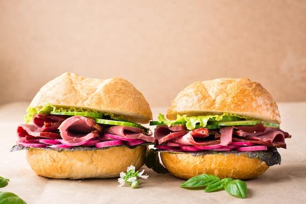 Alguns hambúrgueres frescos com pastrami, pepino, rabanete e ervas em papel artesanal. fast food americano. copie o espaço