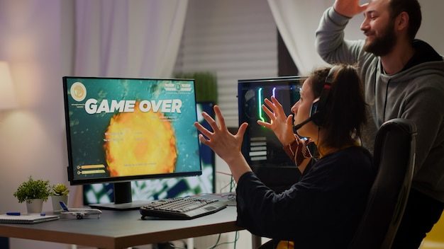 Alguns jogadores estressados perdem o videogame de atirador espacial jogando em um computador rgb poderoso durante o streaming de uma competição online. mulher cibernética profissional com fone de ouvido em casa durante o torneio virtual