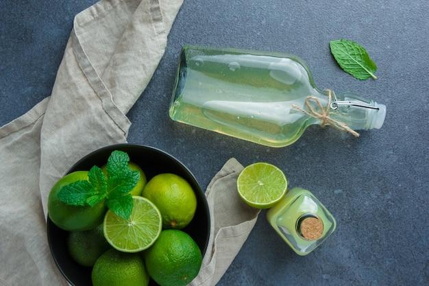 Alguns limões verdes com suco de limão em uma tigela preta no pano de tecido branco na superfície escura, plana leigos.