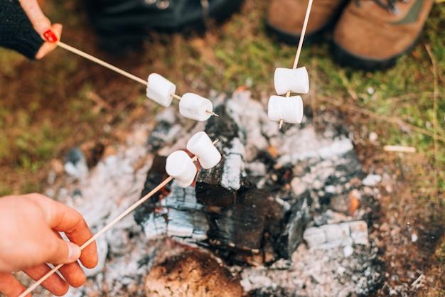 Alguns marshmallows acima de uma lenha em chamas no campo