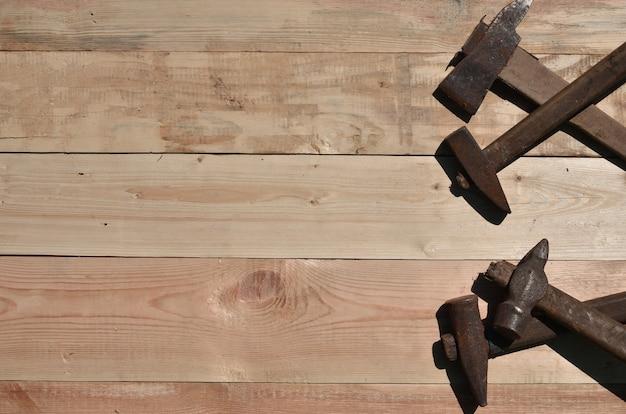 Alguns martelos enferrujados encontra-se em uma mesa de madeira em uma oficina