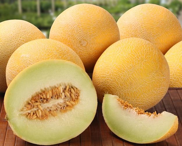 Alguns melões sobre uma superfície de madeira. frutas frescas.