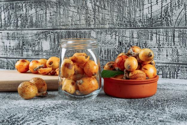 Alguns nêspera em uma jarra, tigela e tábua em plano de fundo texturizado cinza, vista lateral.