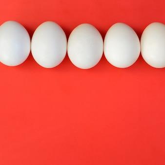 Alguns ovos brancos sobre um fundo vermelho brilhante