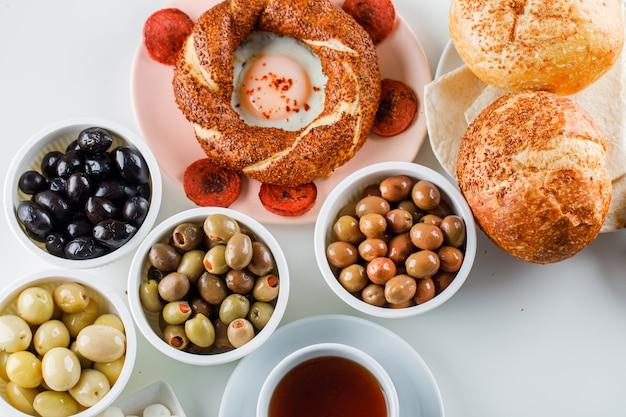 Alguns ovos com linguiça com uma xícara de chá, pão turco, azeitona, pão em um prato na superfície branca, vista superior