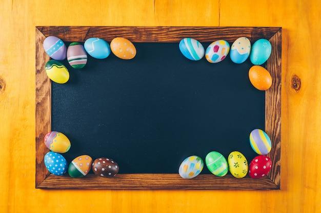 Alguns ovos da páscoa no quadro preto no fundo de madeira amarelo, vista superior.