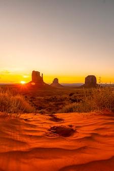 Alguns passos na areia vermelha ao amanhecer de monument valley, utah. foto vertical