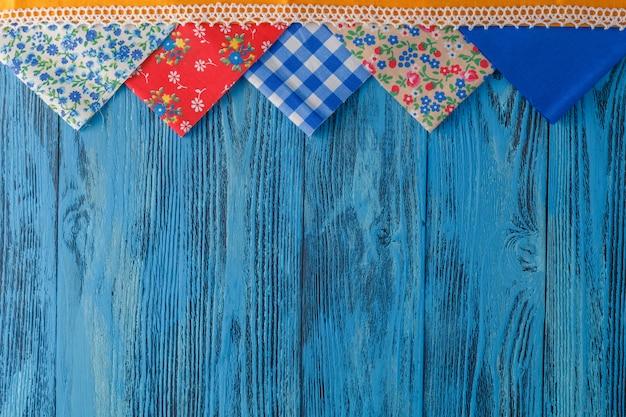 Alguns pedaços de tecido no fundo da mesa azul