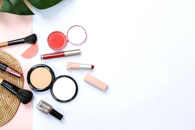 Alguns produtos cosméticos com fundo de papel de cor de rosa e branco doce