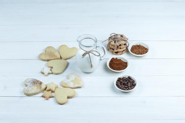 Alguns tipos diferentes de biscoitos com grãos de café, café instantâneo, cacau, jarro de leite no fundo da placa de madeira branca, vista de alto ângulo.