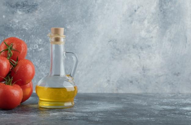 Alguns tomates suculentos com uma garrafa de vidro de óleo.