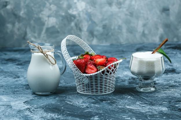 Alguns, uma cesta de morangos com uma jarra de leite e uma tigela de vidro de iogurte sobre fundo de mármore azul escuro, close-up.