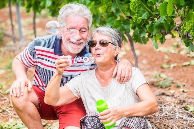 Alguns viajantes maduros alternativos soprando bolhas de sabão em um vinhedo