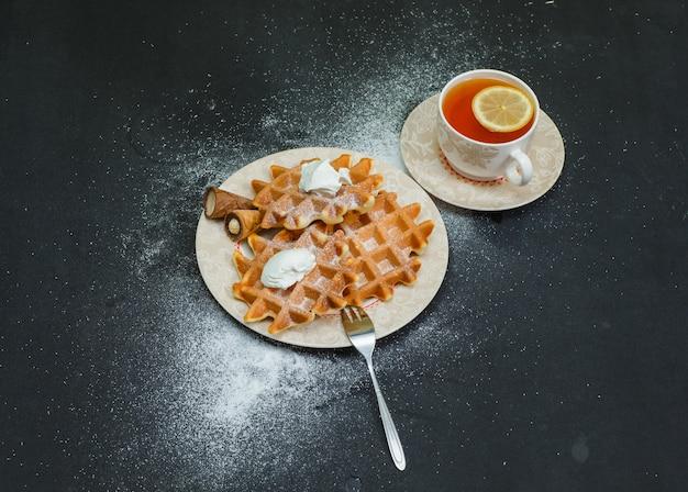 Alguns waffles com chá em um prato na vista escura e de alto ângulo.