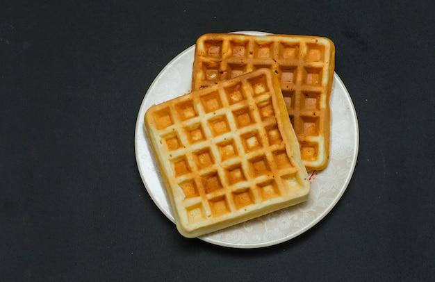 Alguns waffles em um prato na vista superior escura.