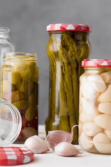 Alho, aspargos e azeitonas conservados em potes de vidro