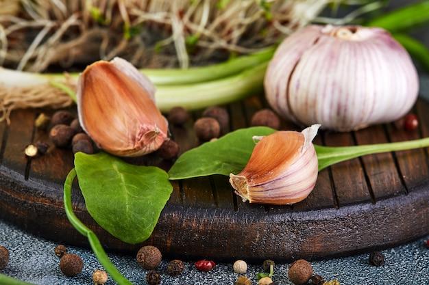 Alho, cebolinha, rudimentos e ervilhas de pimenta em uma madeira