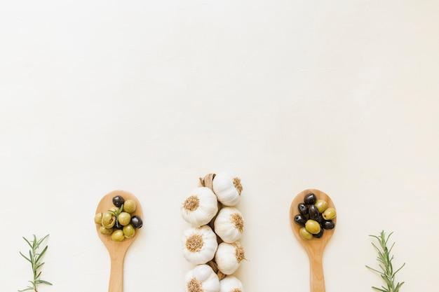 Alho e azeitonas em colheres de madeira