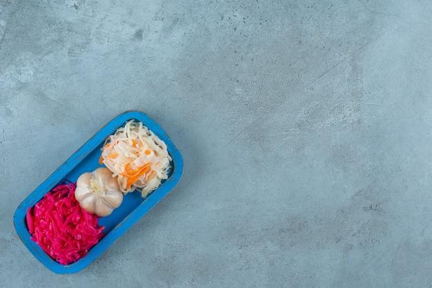 Alho e chucrute em uma placa de madeira, na mesa de mármore.