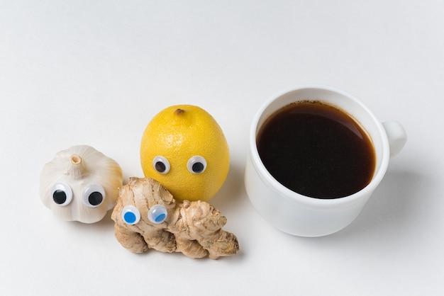 Alho e limão gengibre com olhos arregalados e xícara de café no fundo branco